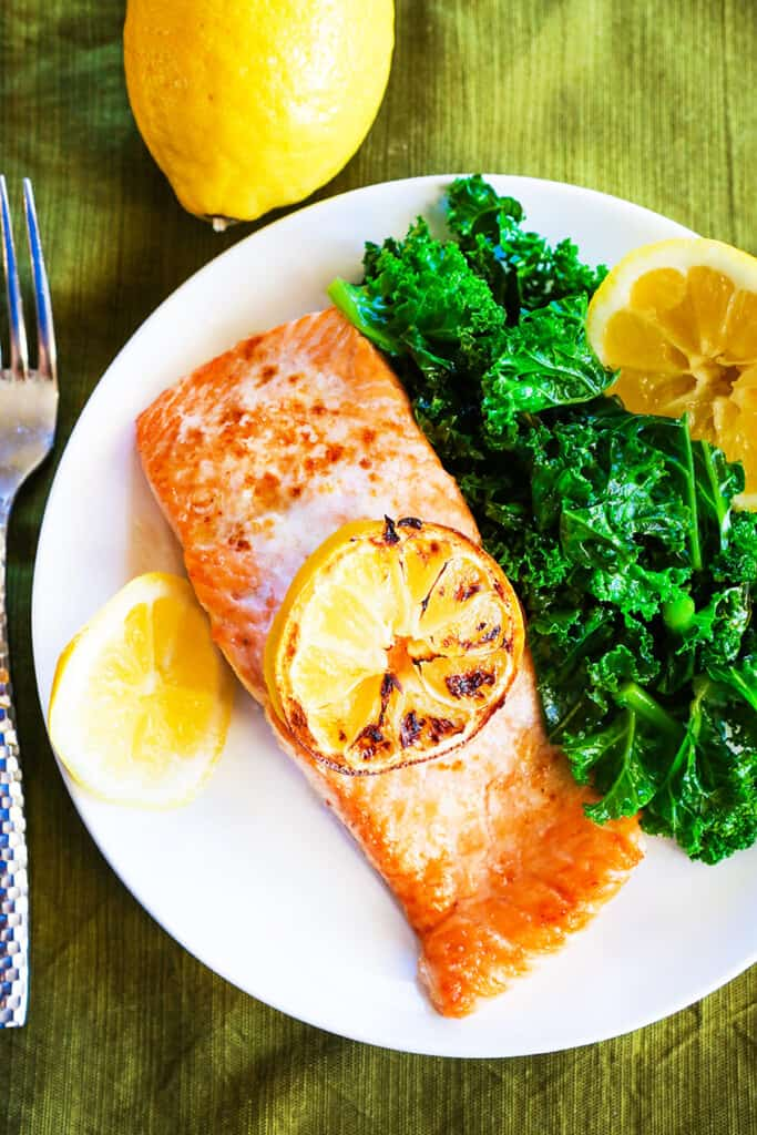 top view of salmon on plate next to sauteed kale and lemon wedges