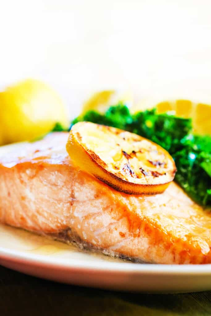 Perfectly cooked fillet of salmon on a plate next to greens