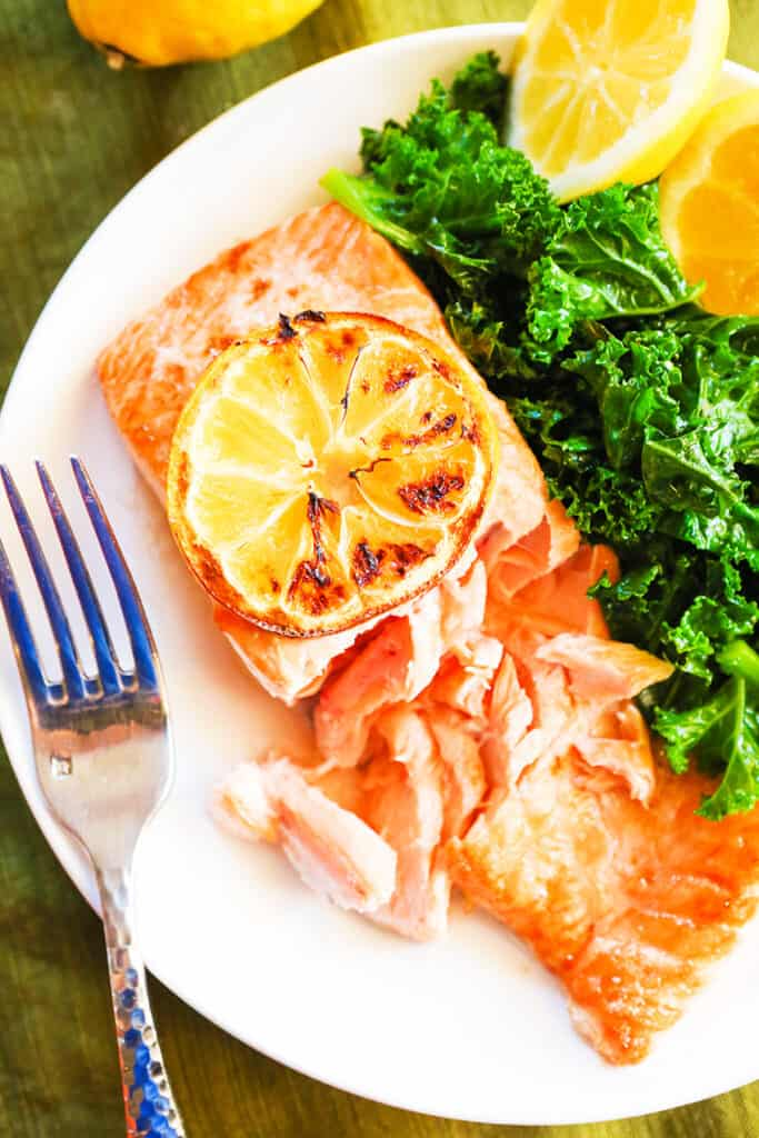 flaked salmon on plate with fork next to it