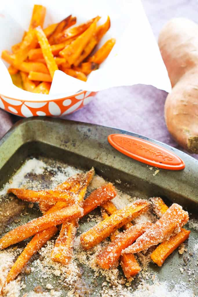 pan of sweet sweet potato fries and savory fries in background