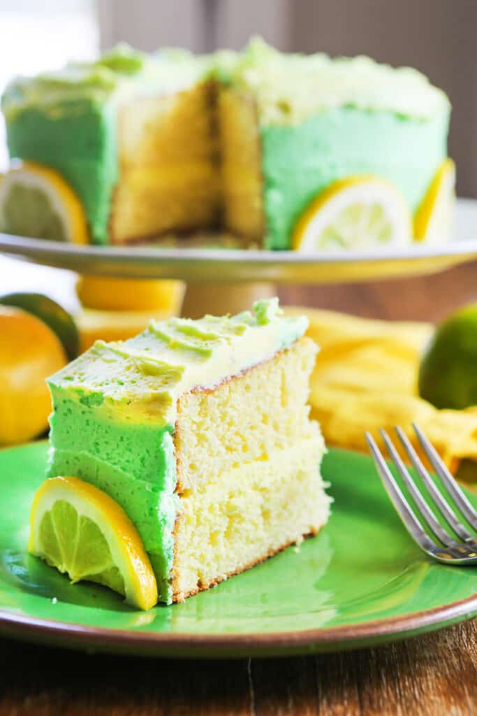 slice of lemon layer cake sitting in foreground next to entire cake