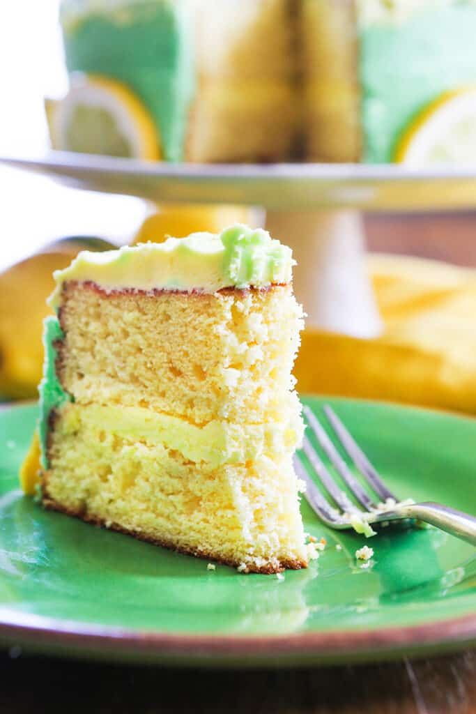 slice of lemon layer cake on green plate with bite taken out