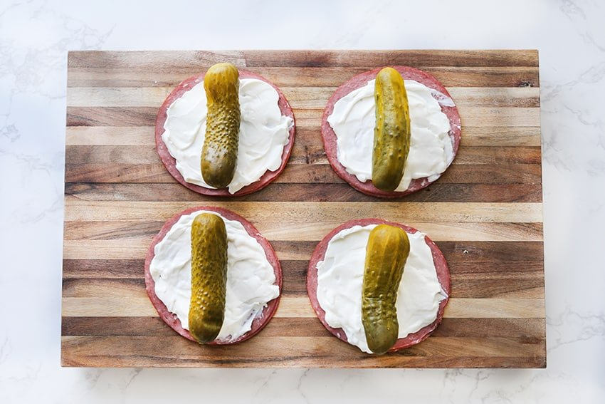 cutting board with corned beef, cream cheese and pickles stacked