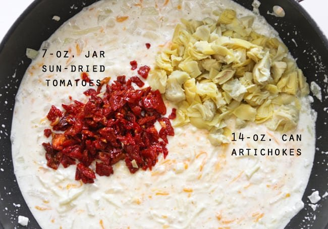 skillet with milk mixture, artichokes and sun-dried tomatoes