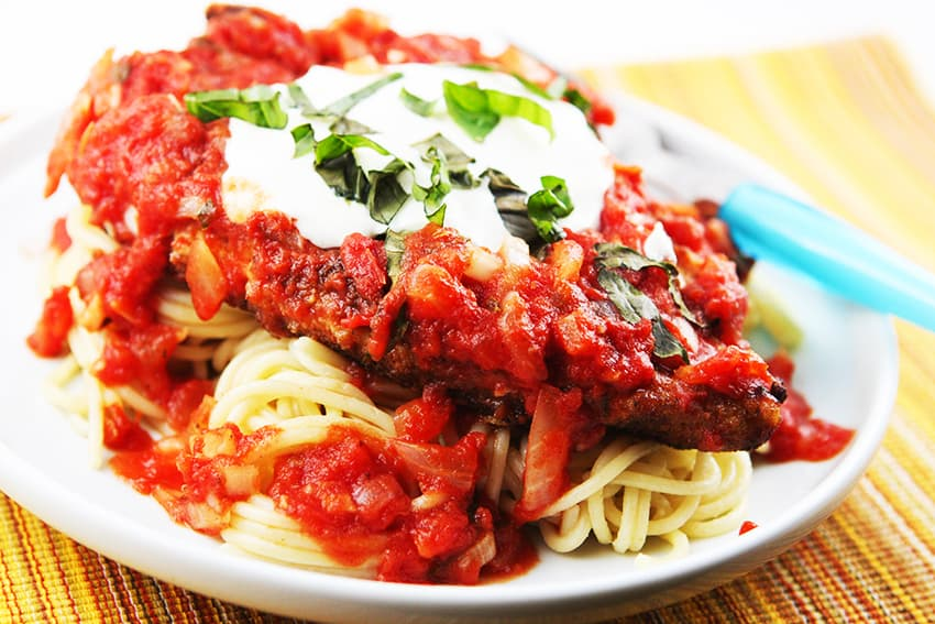 plate of chicken parmesan over spaghetti noodles