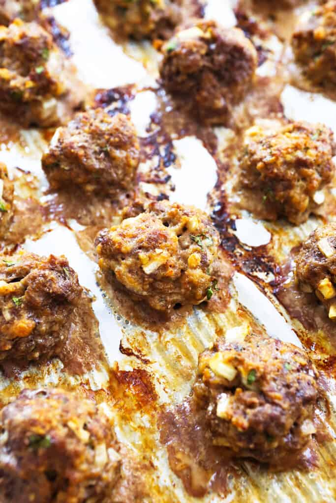 baked meatballs lined up on a baking sheet just out of the oven