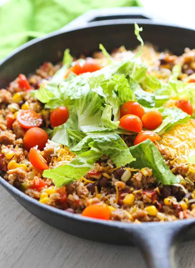 skillet with cooked rice and beans and fresh lettuce and tomatoes on top