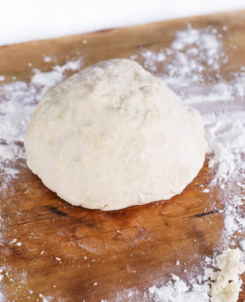ball of pizza dough sitting on a cutting board dusted with flour