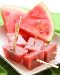 watermelon cubes with toothpicks on them sitting on a plate.