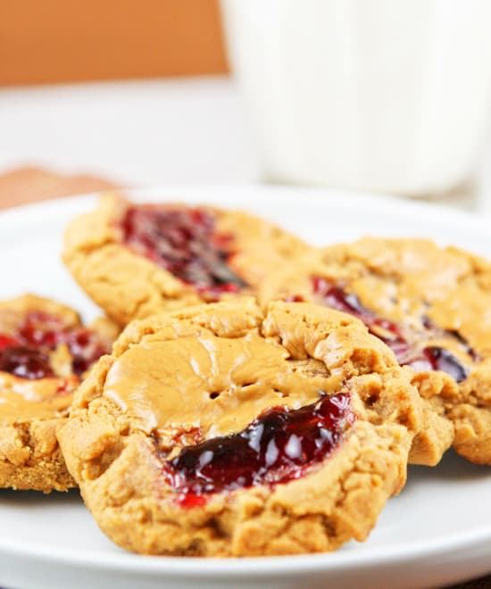 plate of peanut butter jelly cookies sitting next to a glass of milk