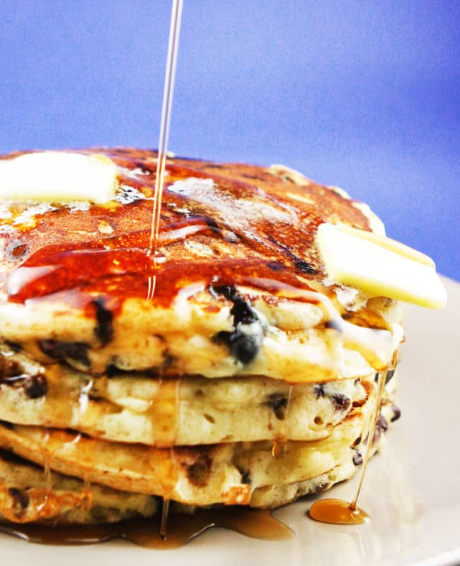 stream of maple syrup being poured over a huge stack of pancakes