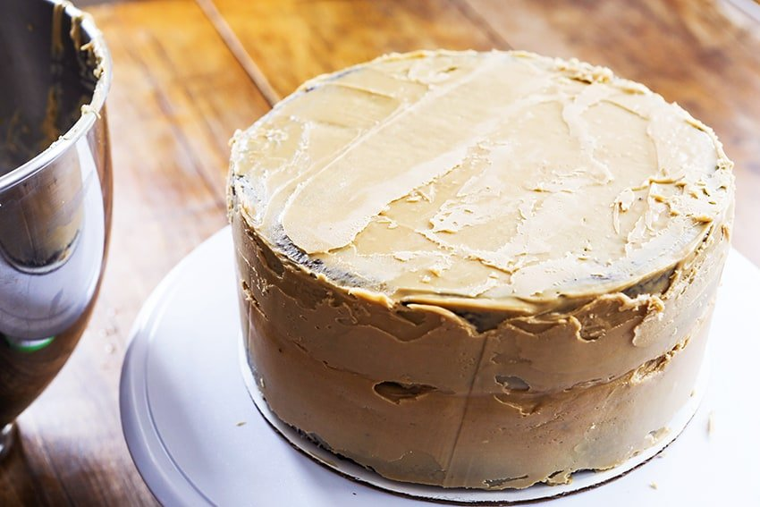 Layer of caramel frosting on a layer cake next to mixing bowl