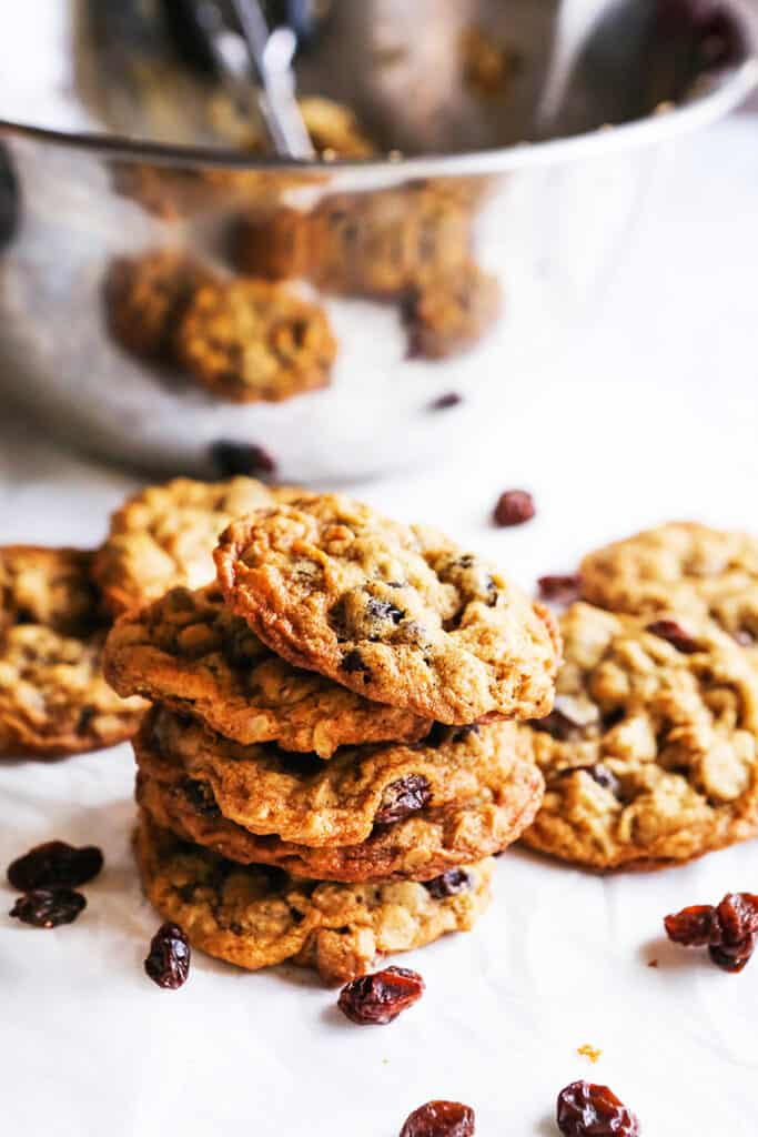 stack of oatmeal raisin cookies sitting next to silver mixing bowl