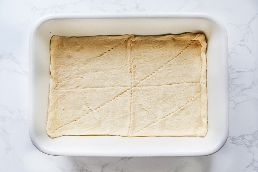 crescent rolls spread on the bottom of a baking dish