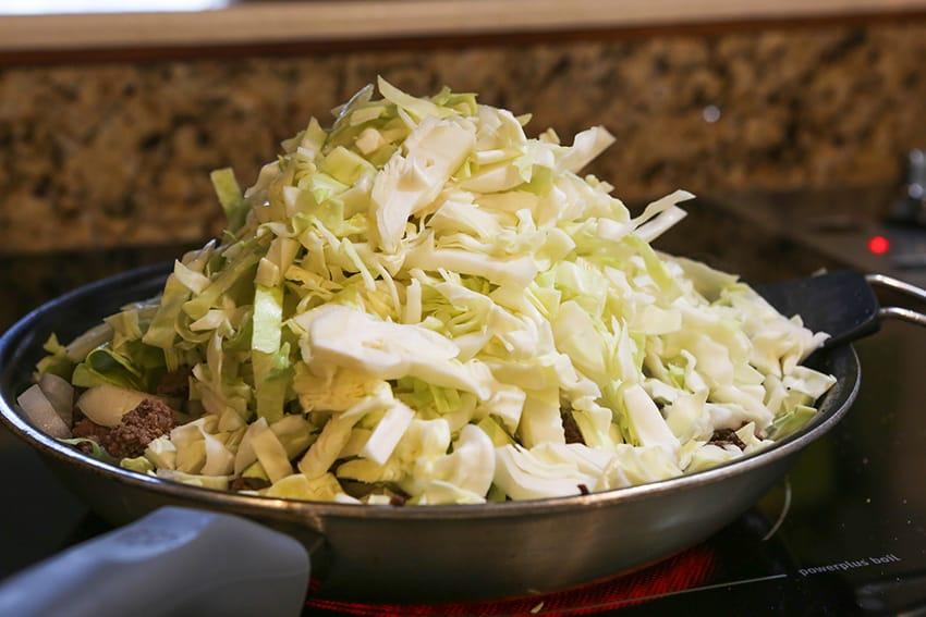 huge pile of shredded cabbage in a skillet