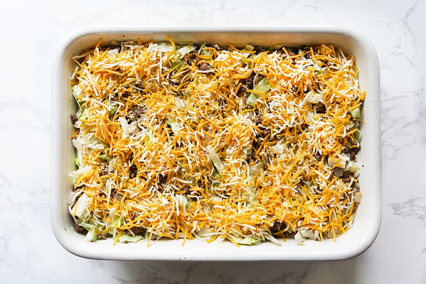 top view of baking dish with ground beef, cabbage and shredded cheese