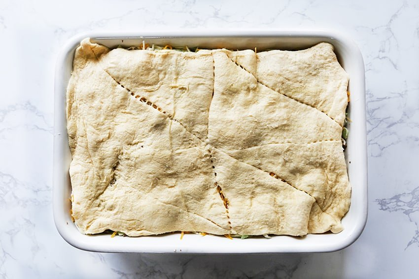 crescent roll dough covering a casserole ready for baking