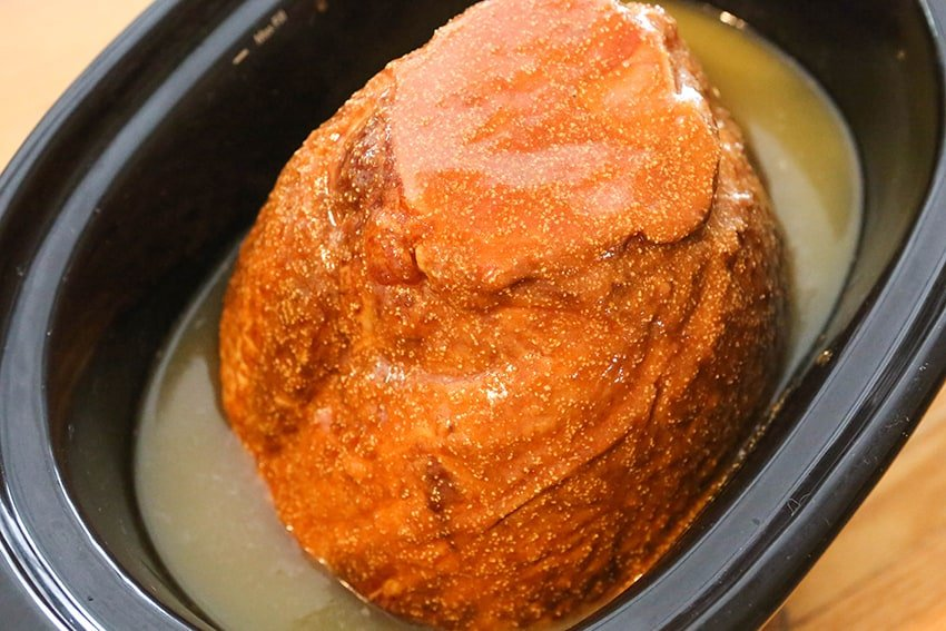top view of ham in crock pot with glaze and pineapple juice