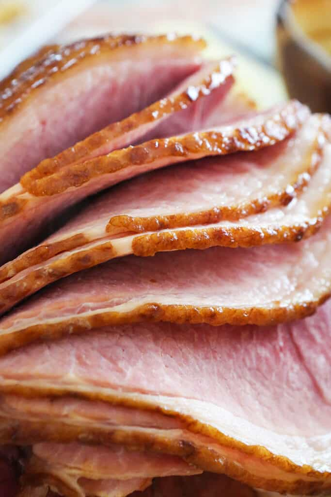 close up of sliced ham folder over other slices and looking ready to eat