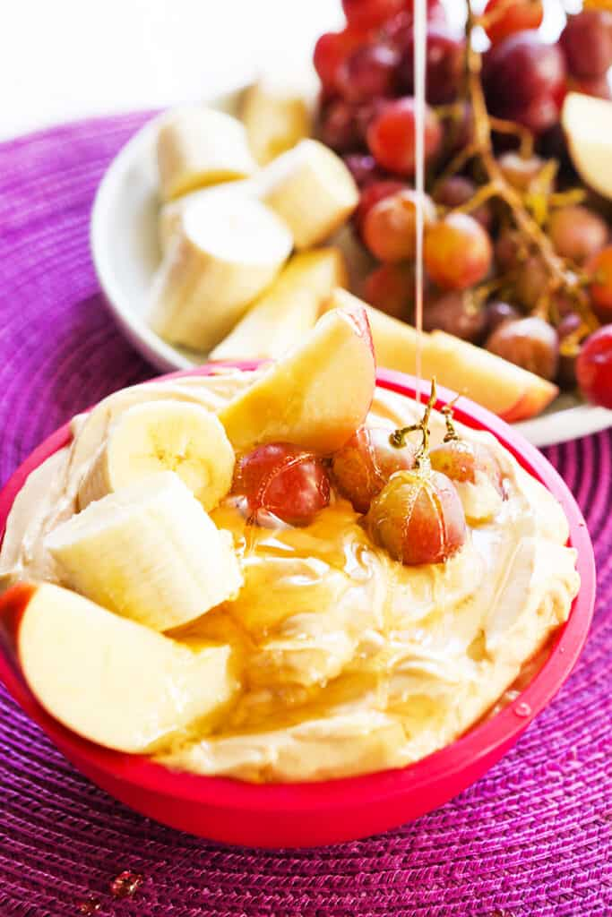 honey drizzling over grapes sitting in a bowl of fruit dip