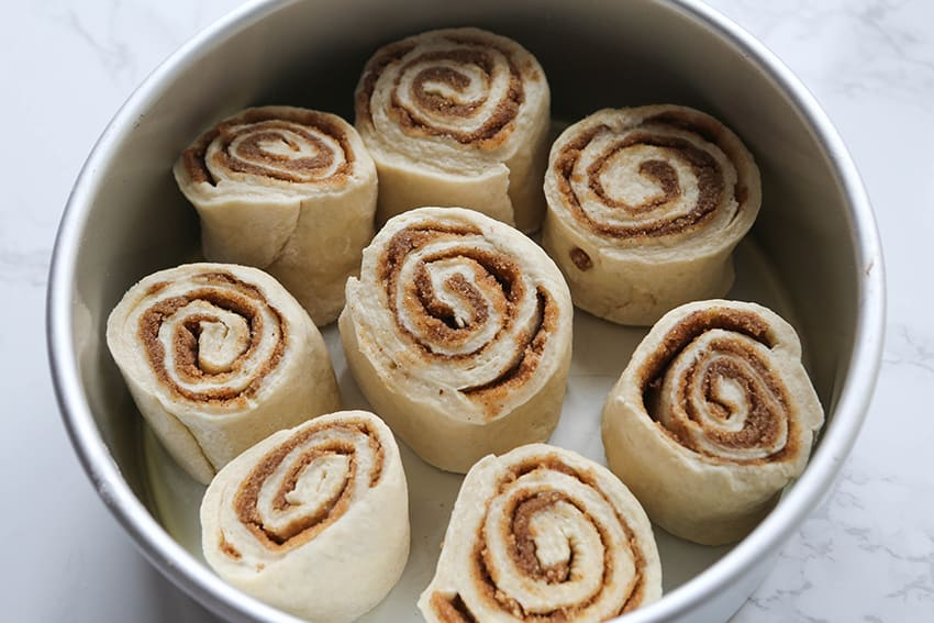 cinnamon roll dough pieces in cake pan ready to bake