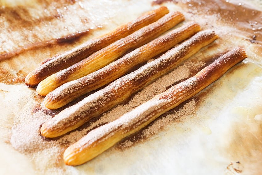 cinnamon and sugar coated churros on parchment paper