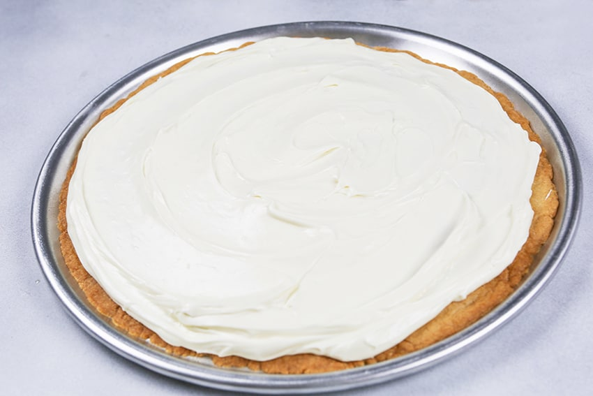 white frosting in a layer on giant cookie on round pizza pan