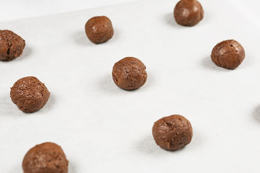 chocolate balls on parchment lined baking sheet