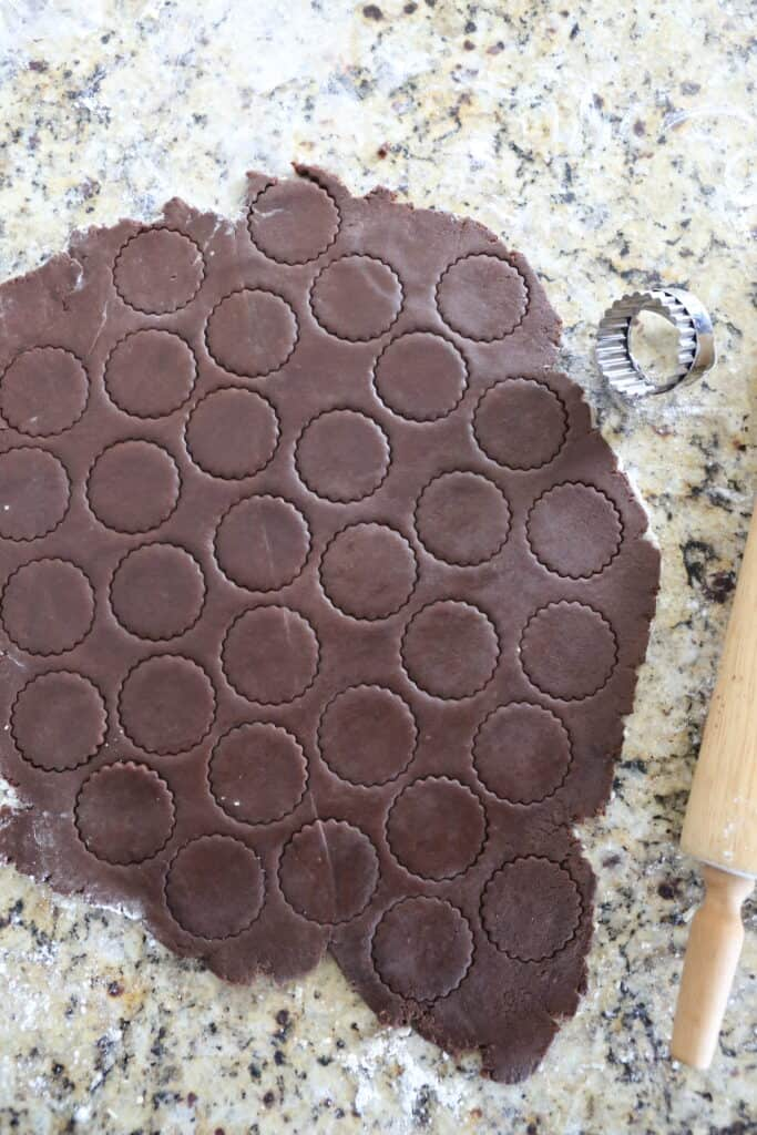 chocolate dough rolled out with circles cut into it and a rolling pin nearby