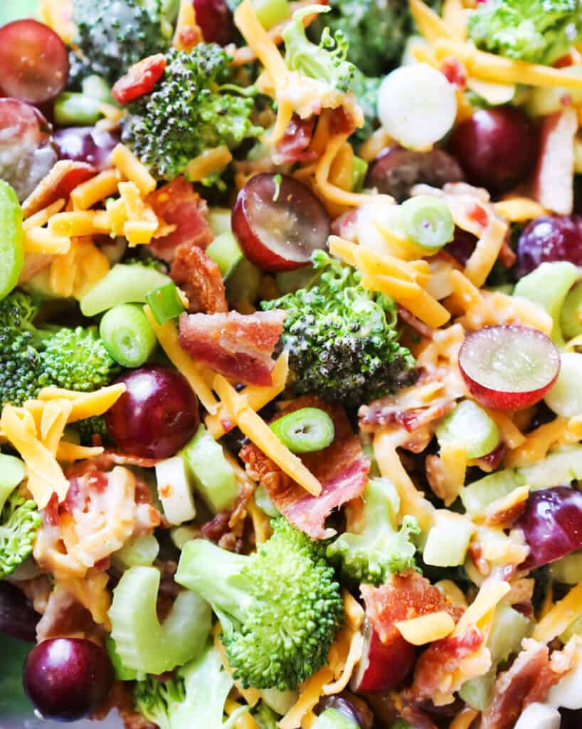 close up top view of broccoli salad with cheese and grapes