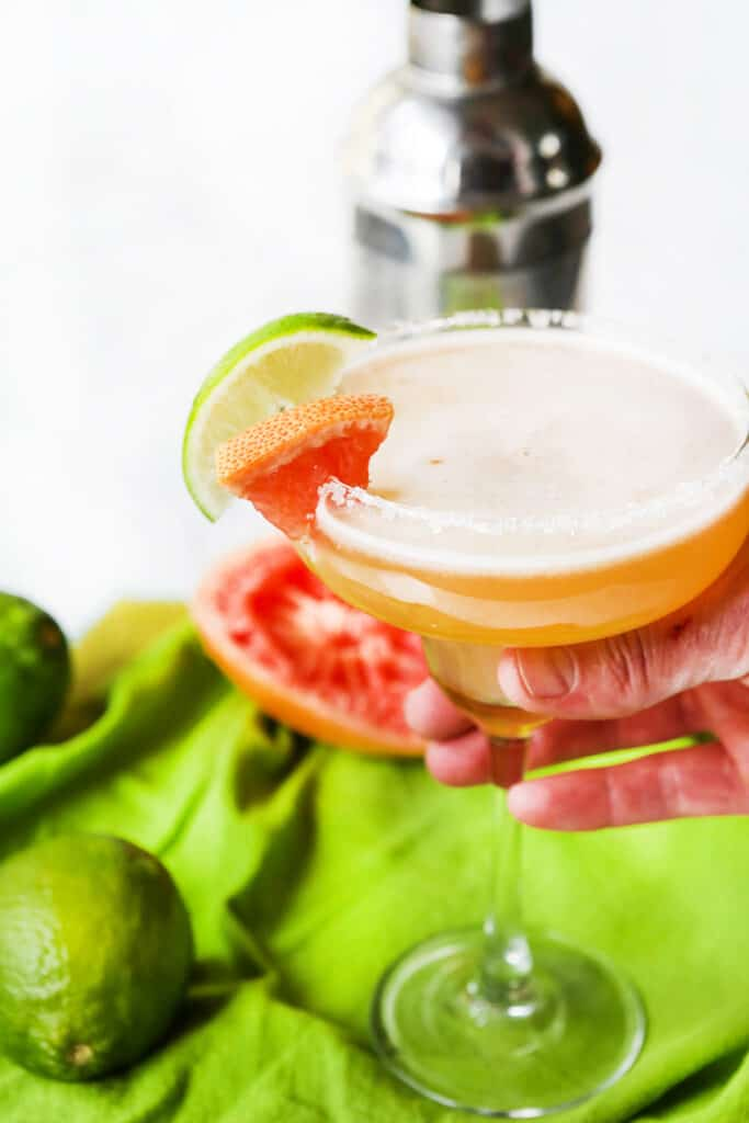 hand holding a margarita with citrus on rim