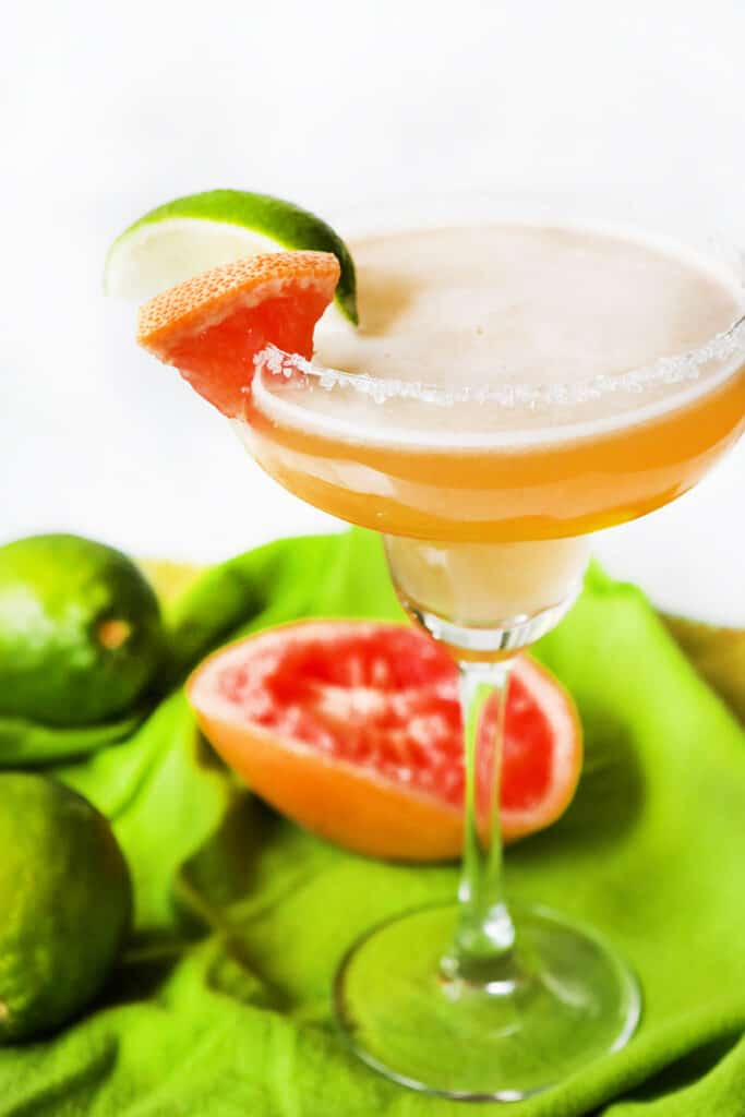 margarita with salt on rim and grapefruit and lime wedges on rim