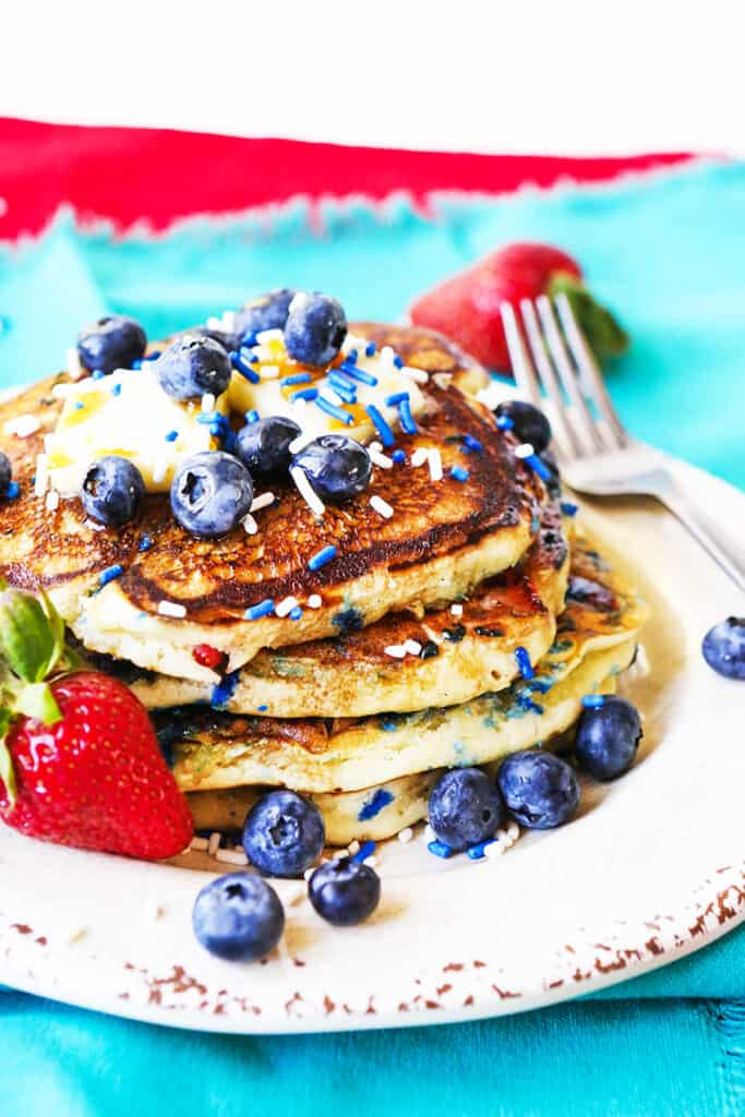 stack of pancakes with blueberries and sprinkles on top sitting next to strawberries