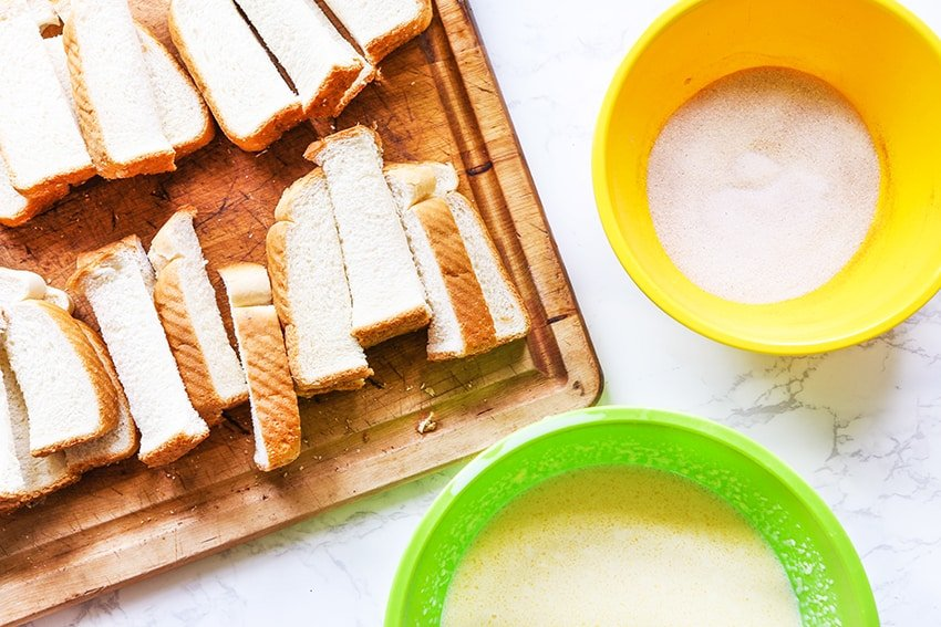 cutting board with bread pieces next to two bowls