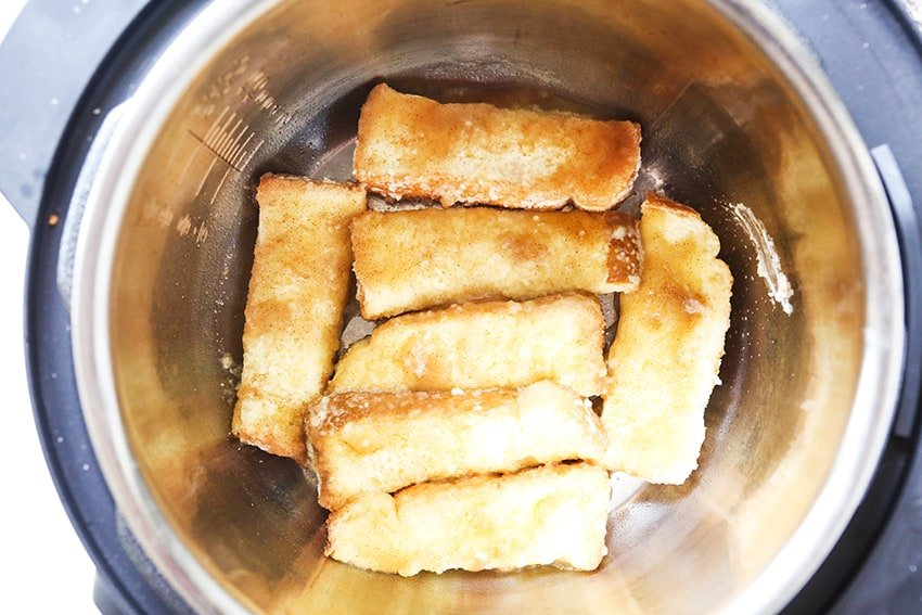 Pieces of French toast in air fryer ready to cook
