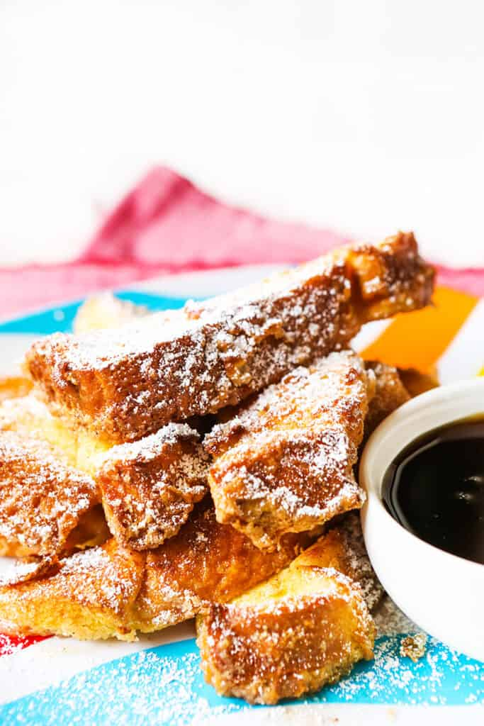 Tall stack of breakfast sticks next to small bowl of maple syrup