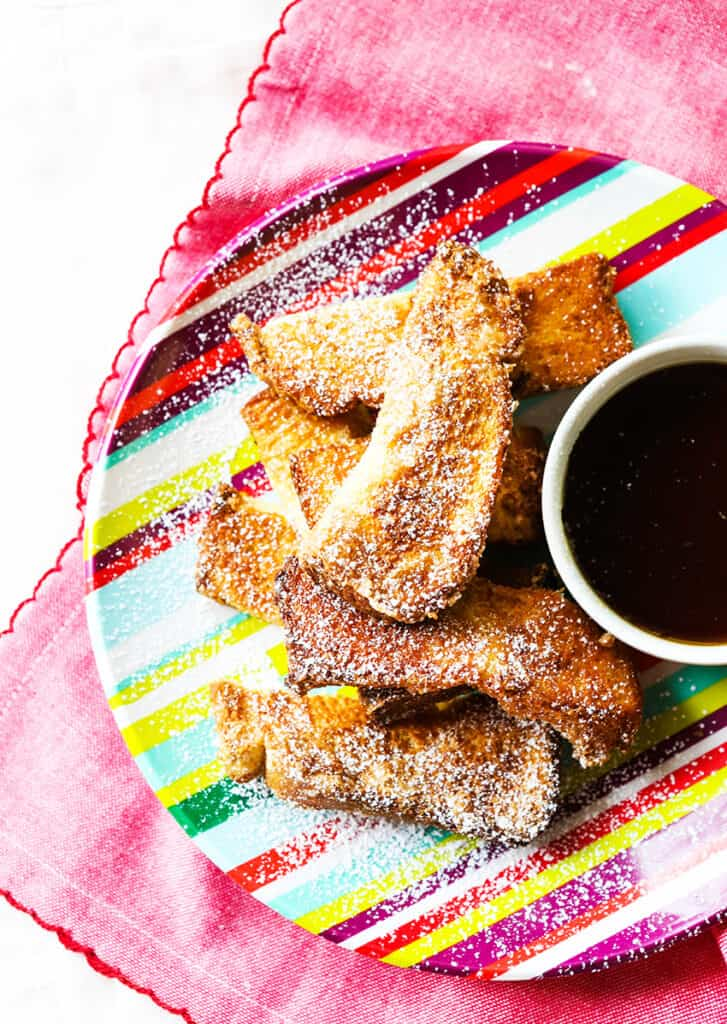 top view of plate of Air Fryer French Toast Sticks sprinkled with powdered sugar