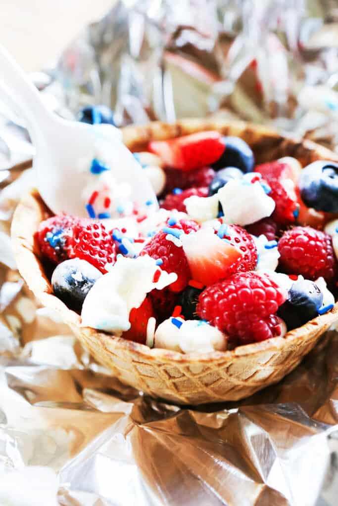 plastic spoon stuck into waffle bowl filled with berries and marshmallows