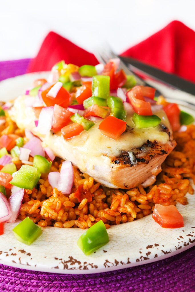 Fiesta lime chicken topped with fresh salsa on a plate