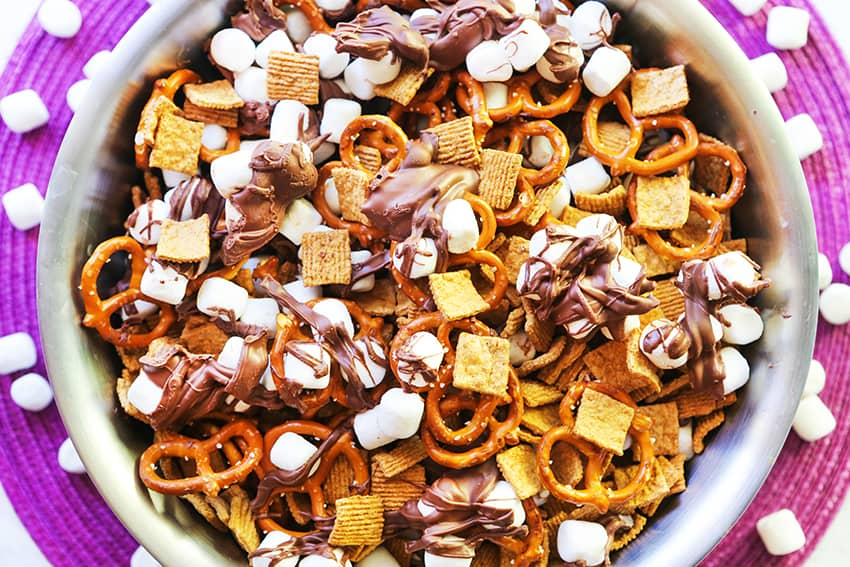 Silver bowl filled with chocolate, marshmallows, cereal and pretzels s'mores snack mix