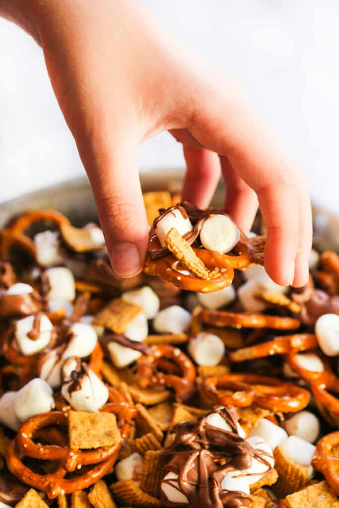 hand grabbing s'mores snack mix out of a bowl