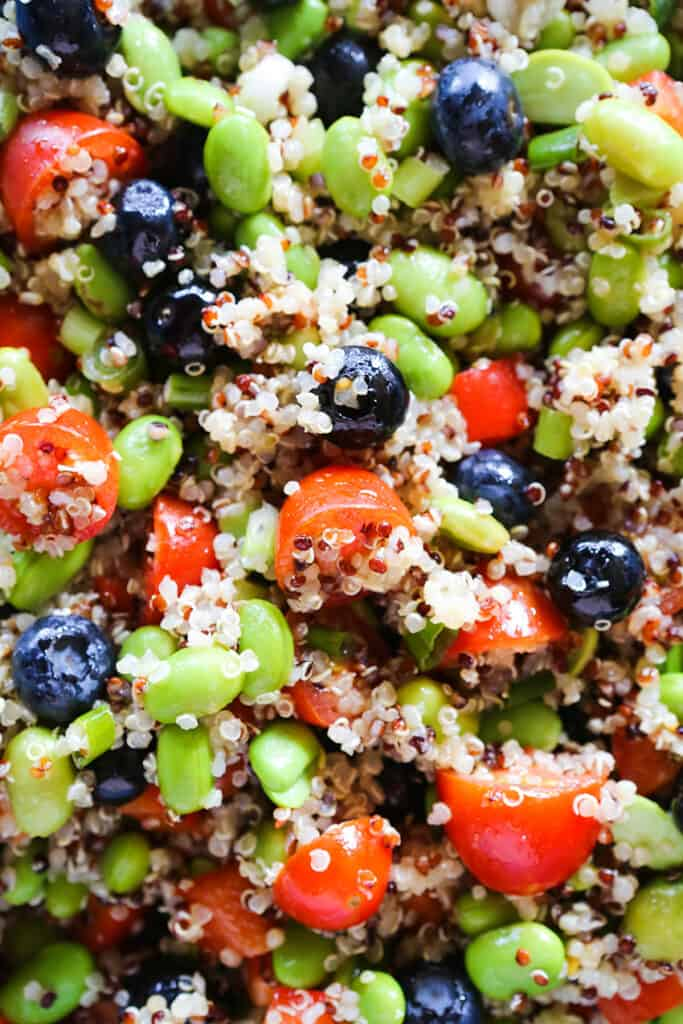 close up of quinoa edamame salad with tomatoes and blueberries