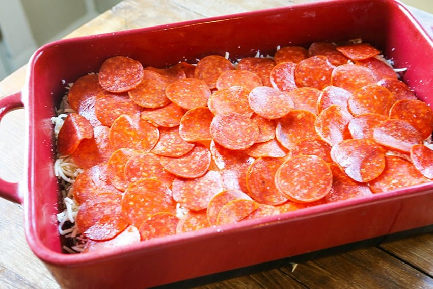 layer of pepperonis stacked in a baking dish