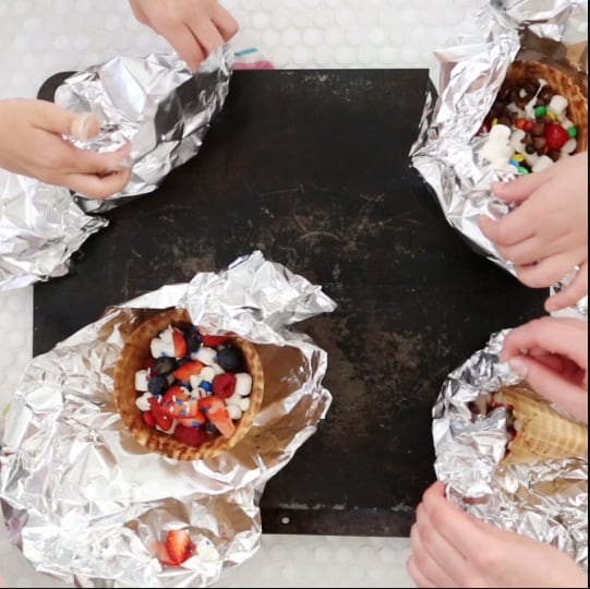 hands folding foil over campfire cones ready to grill