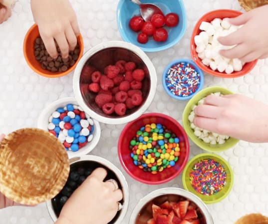 hands reaching into bowls of various ice cream toppings