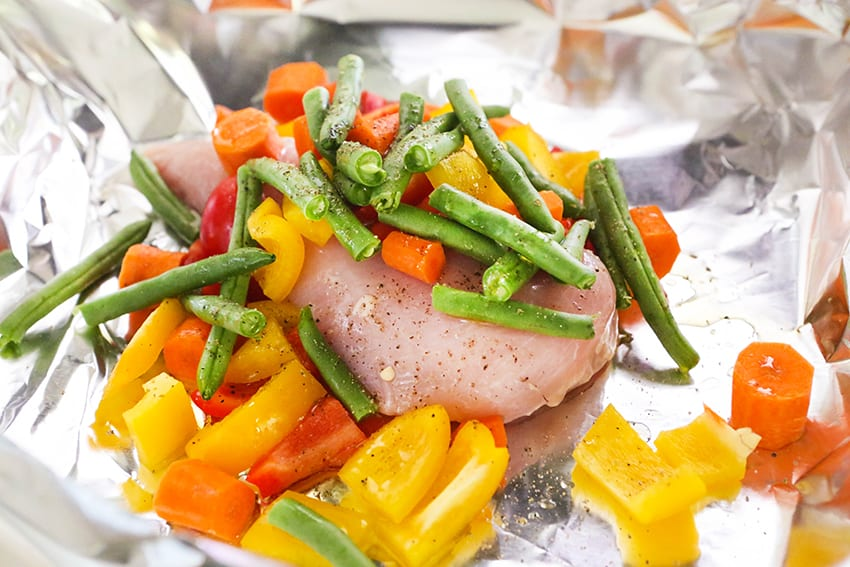 chicken breast on foil with veggies surrounding it