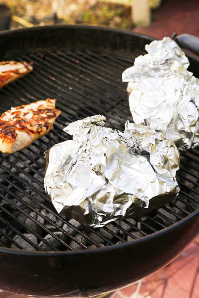 foil pouches on grill next to grilled chicken breasts