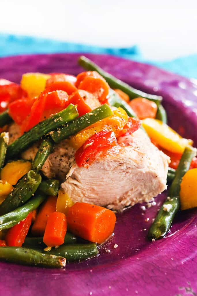 plate of cooked chicken topped with colorful veggies