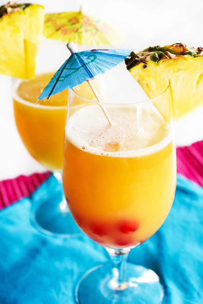 two tropical drinks with pineaplle wedges and drink umbrellas