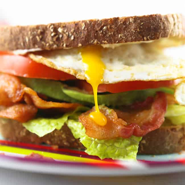 drippy egg yolk coming out of a stacked blt with a twist sandwich
